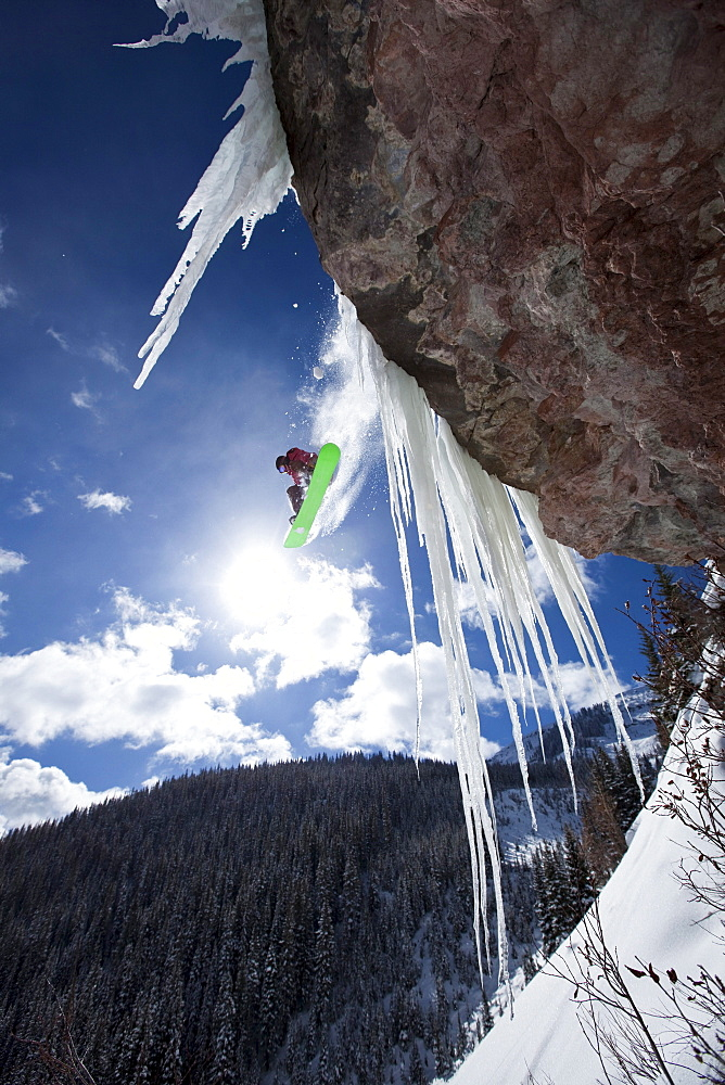 A male snowboarder jumps off an ice waterfall cliff on a sunny day in Colorado.