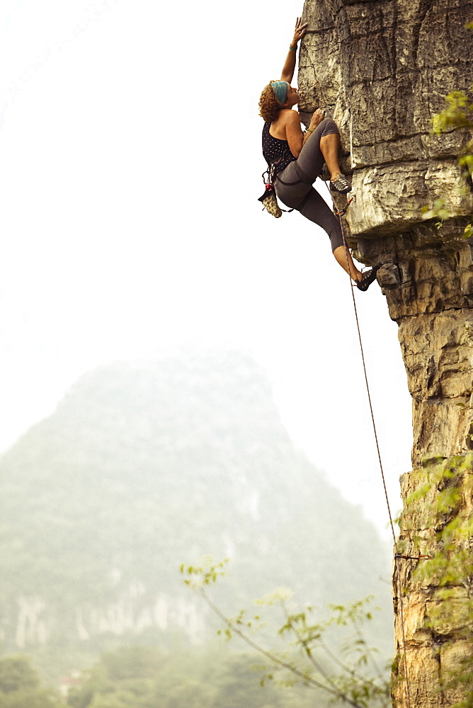 Female climber reaching out for a distant hold on overhanging limestone in China.