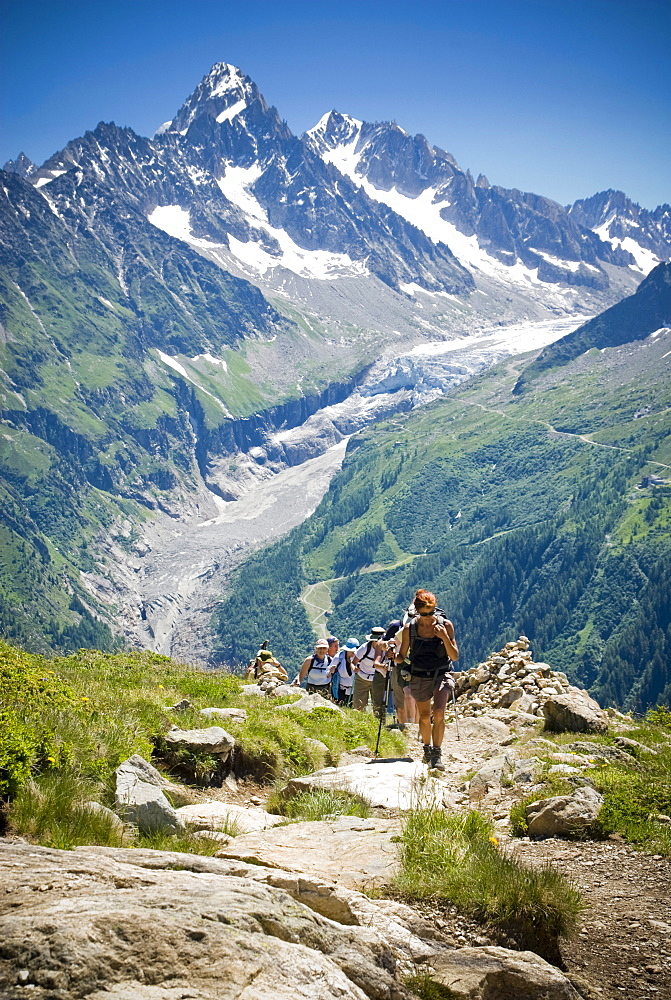 Hikers trek up a hill as the majesty of the Alps towers in the background.