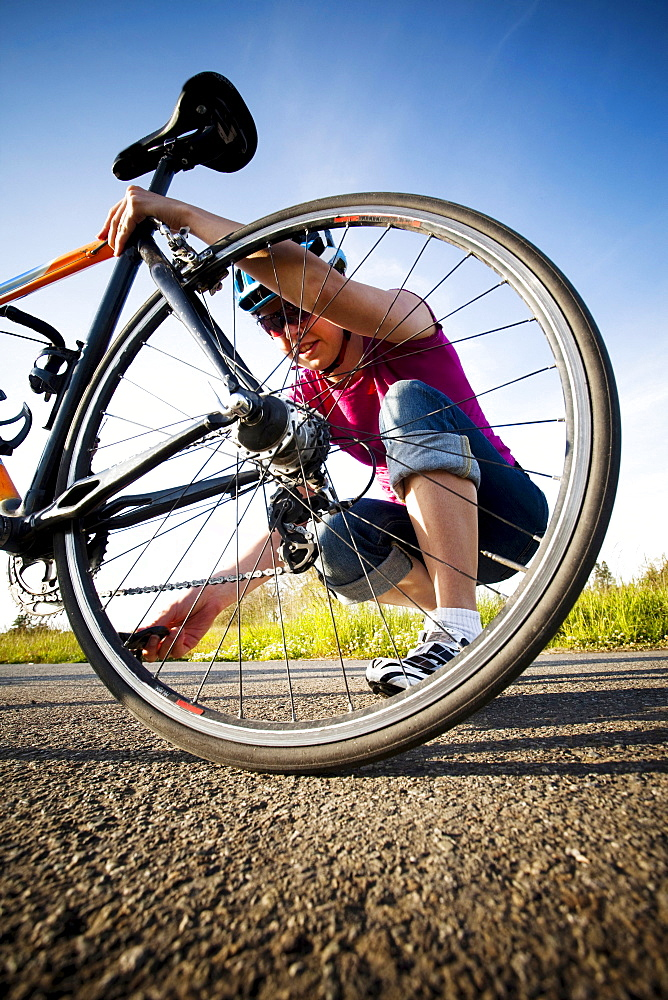 A young woman inspects her chain and back tire on the way home from work on her commuting bike.