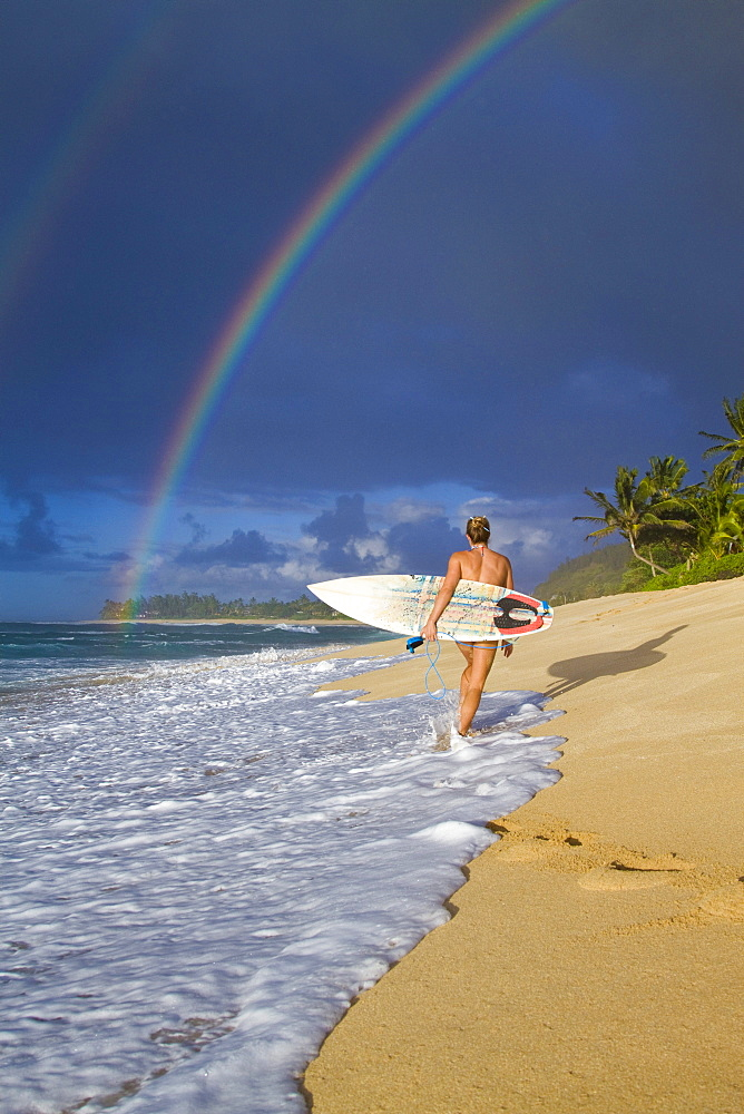 An amazing rainbow over Rocky Point, as a surfer girl walks along the beach, on the north shore of Oahu, Hawaii.