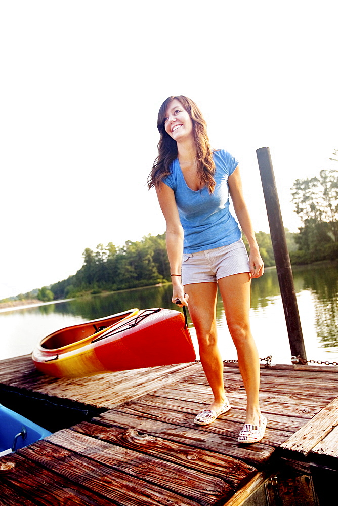 Young woman smiling pulling a kayak out of the water and onto a pier at a lake at Oak Mountain State Park, Pelham, AL.