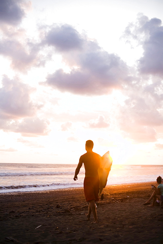 A man walks out to the ocean with his surfboard as the sun sets.