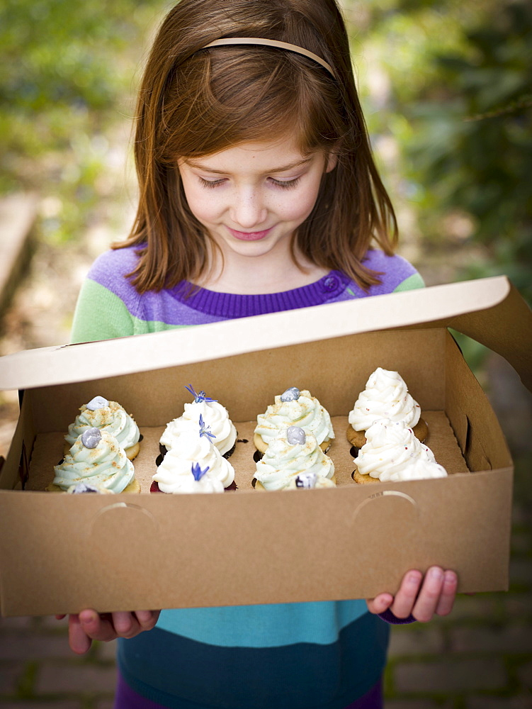 girl holds box of cupcakes