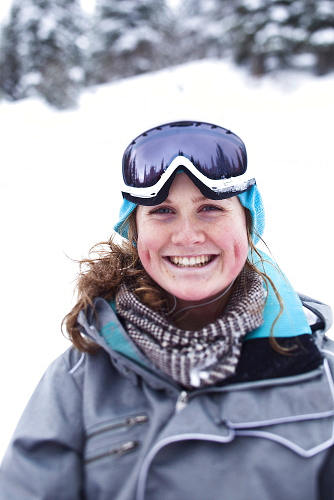 A happy young woman smiles while taking a break from skiing at Schweitzer Mountain in Sandpoint, Idaho.