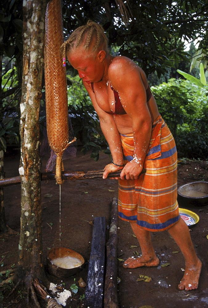 Albino Saramaka Maroon woman squeezing manioc to leach it in Likorio village on the Suriname River, Suriname
