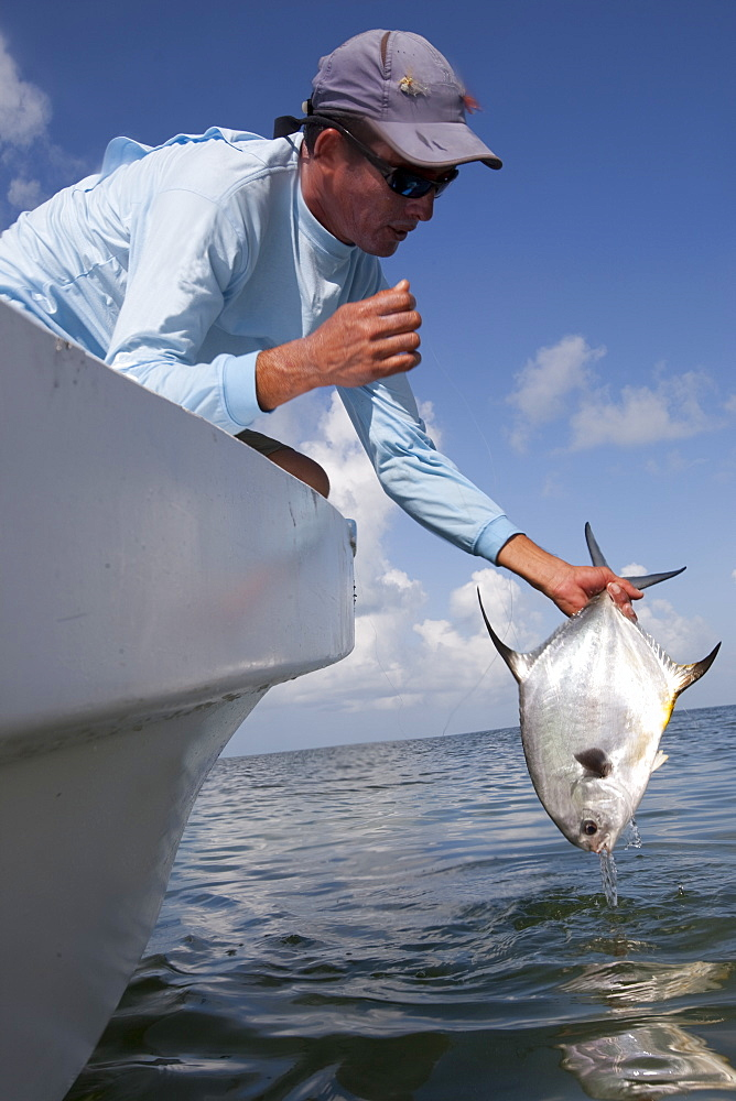 a fisherman holds up a freshly caught permit fish from the bow of his flats boat, San Pedro, Belize