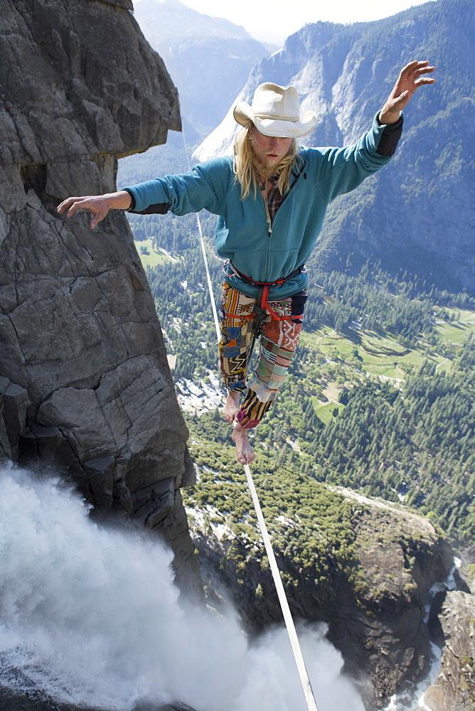 Male highliner walking the Yosemite Falls highline, Yosemite Valley, California, United States