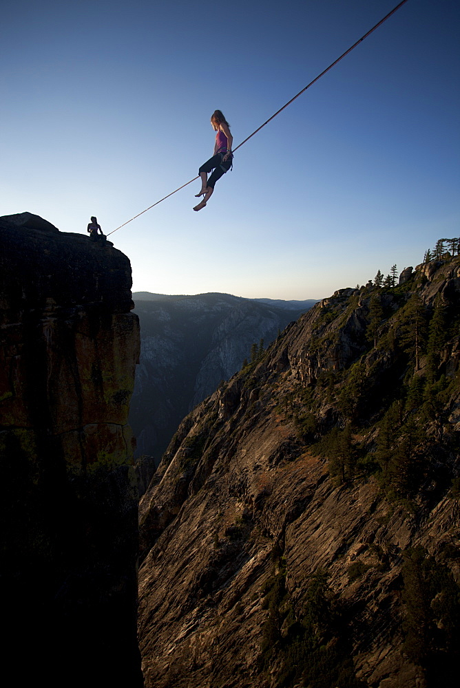 Female highliners sitting on the highline and anchor above the Yosemite Valley floor at Taft Point, Yosemite National Park, California, United States