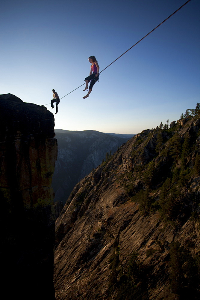 Female highliners simultaneously sitting on a highline above the Yosemite Valley floor at Taft Point, Yosemite National Park, California, United States