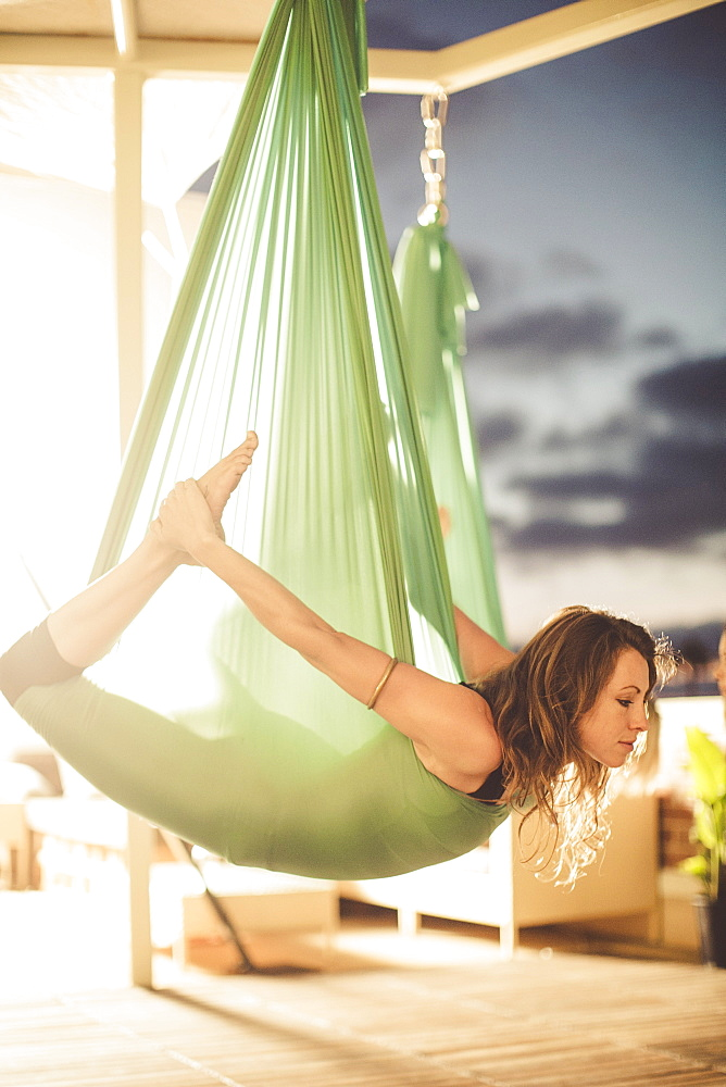A lady performs aerial yoga, La Jolla, CA, USA