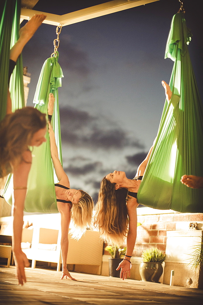 Three young ladies perform aerial yoga, La Jolla, CA, USA