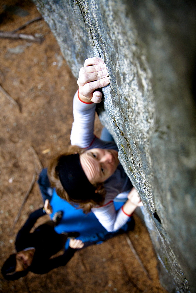 A female rock climber reaches out while on a boulder climb in Pemberton, British Columbia, Canada, Pemberton, British Columbia, Canada