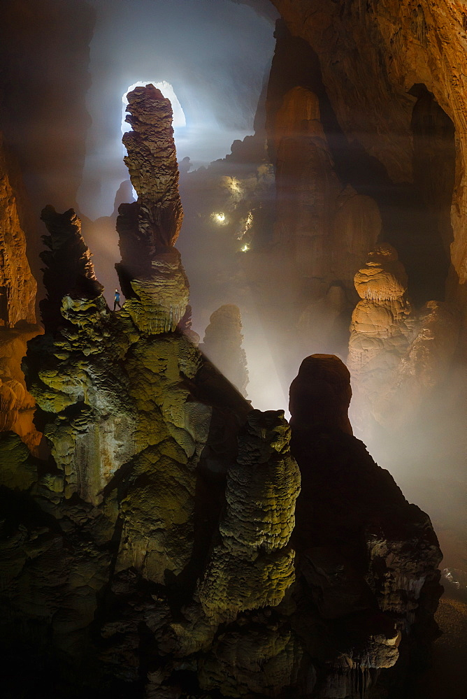 A caver is dwarfed by massive stalagmites in Hang Son Doong. Light can be seen coming in in the distance through the frist doline which is over 3 km away. Hang Son Doong is located in Phong Nha Ke Bang National Park, Vietnam.