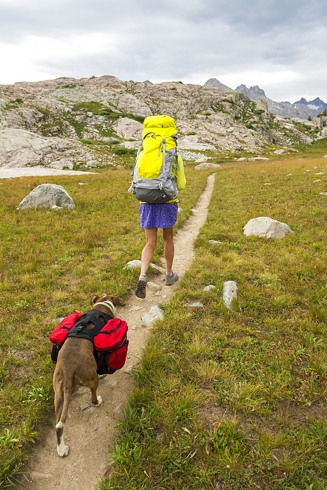 A woman and her dog hiking along trail into Titcomb Basin in the Wind River Range, Bridger Teton National Forest,  Pinedale, Wyoming.