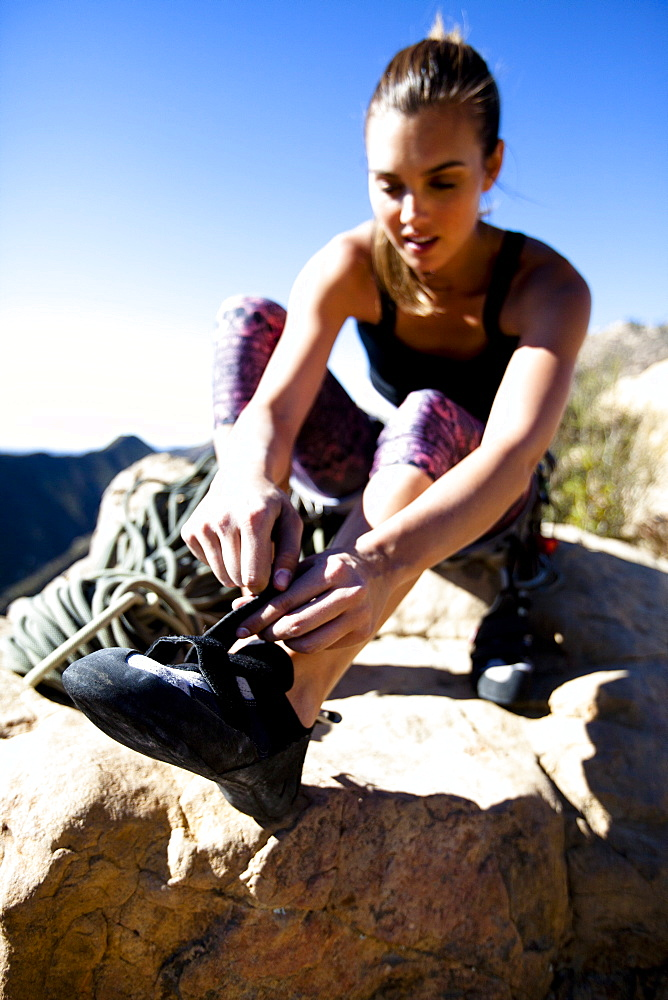 A female climber puts on her climbing shoes while sitting on top of Lower Gibraltar Rock in Santa Barbara, California. Lower Gibraltar Rock provides great vistas of Santa Barbara and the Pacific Ocean.
