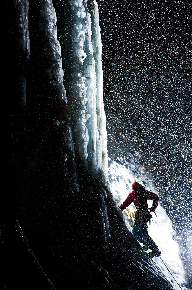 An ice climber checks his gear before starting a climb at night in Provo Canyon.