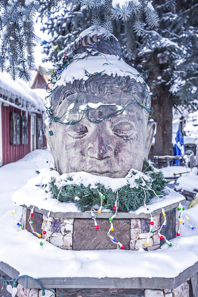 A snow covered Buddah statue in the town of Crested Butte, Colorado, during the holidays.