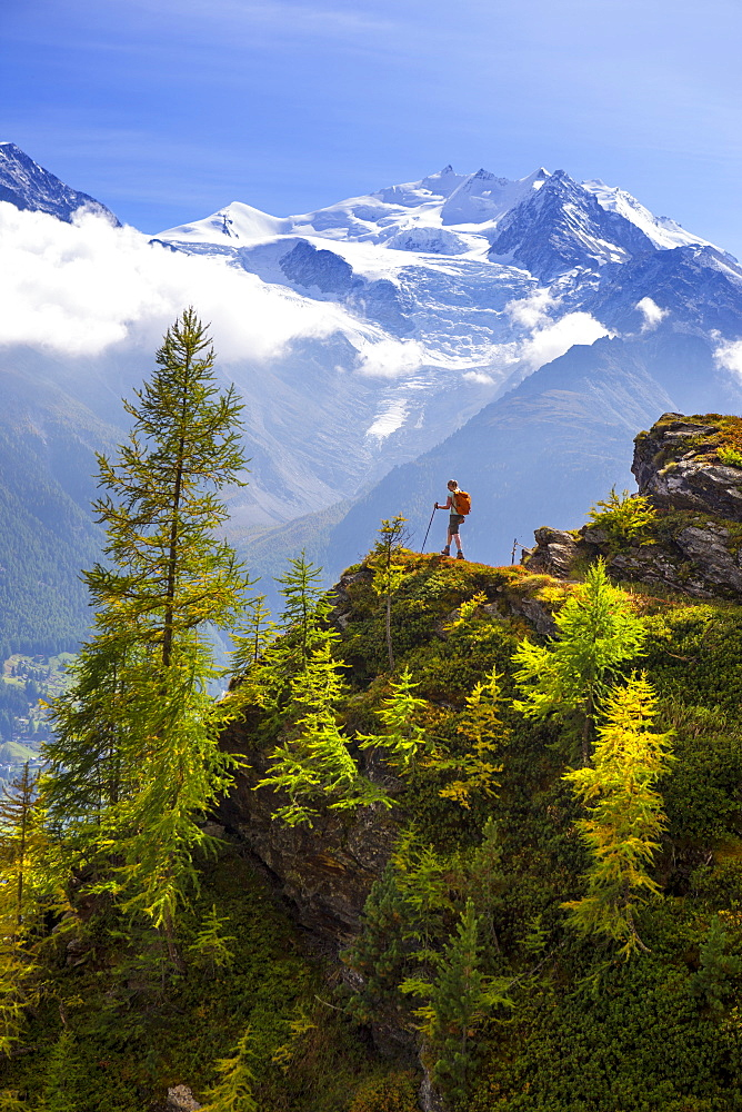 A female hiker is enjoying the view near Embd, in the Swiss Alps. This region of Wallis, close to Zermatt, is famous for the outdoor activities one can do. It is a paradise for hikers, climbers, mountainbikers and nature lovers. In the background the Nadelgrat range, with the Ried glacer coming down the hill.