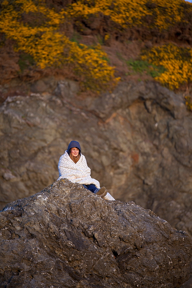 A young woman wrapped in a blanket sists on a rock bluff at Bandon Bay, Oregon.