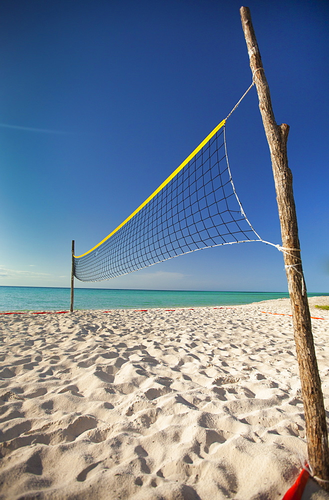 Two rough sticks hold up a beach volleyball net set up beside the ocean on Playa La Jaula beach, Cayo Coco, Cuba.