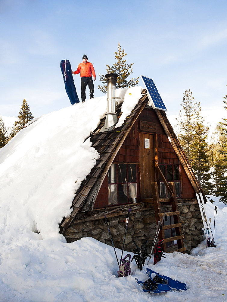 Man prepares to another sled run off the roof of the Peter Grubb ski hut, Sierra Nevada