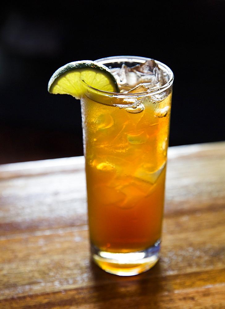 Iced tea with lime sitting on a bar.