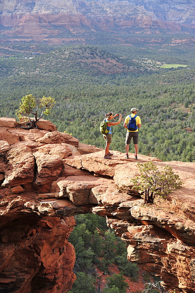 Hikers on the Devil's Bridge in Red Rock-Secret Mountain Wilderness Area outside Sedona, Arizona May 2011.  The Devil's Bridge is an easy two-mile hike with spectacular views.