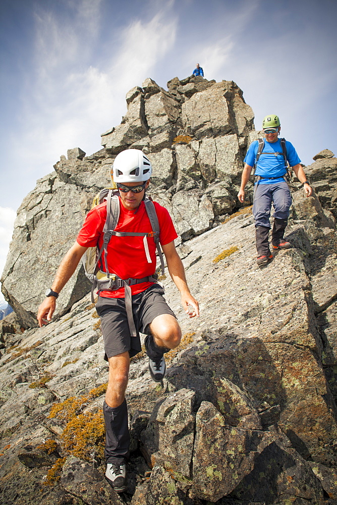 Three climbers descend from the summit of Trio Peak, British Columbia, Canada.