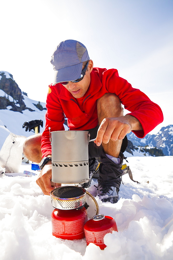 A climber uses a camping stove to make his dinner while camping in the mountains.