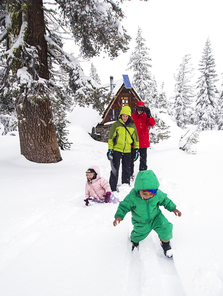 Parents and kids play in fresh snow in front of the Peter Grubb ski hut, Sierra Nevada
