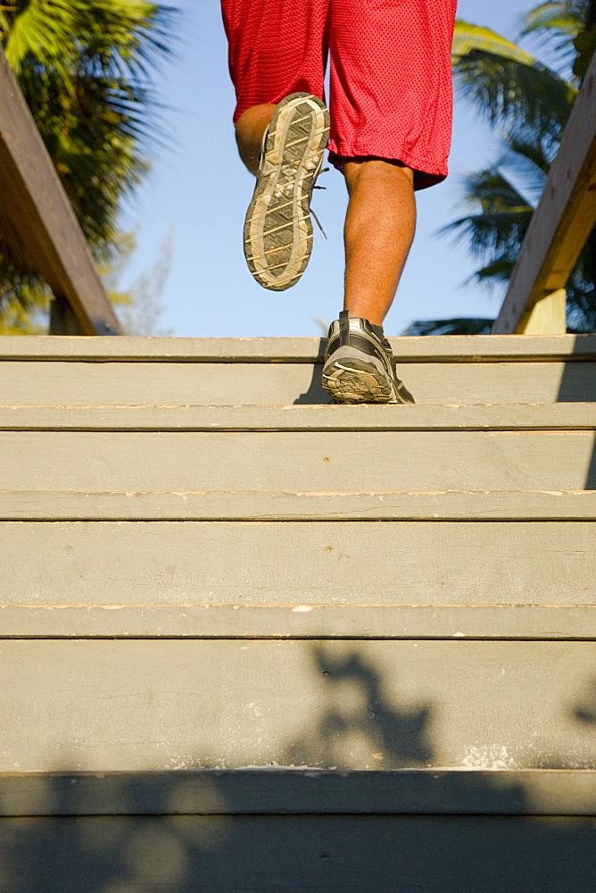 A man's legs as he runs up stairs of an outdoor boardwalk, tropical setting