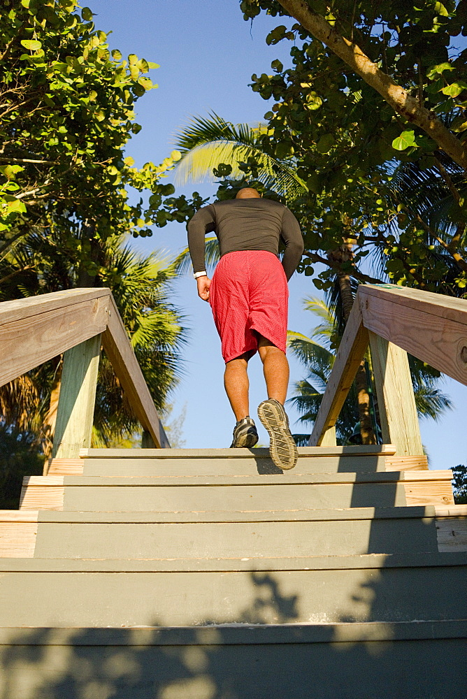 A man runs up stairs of an outdoor boardwalk in a tropical setting