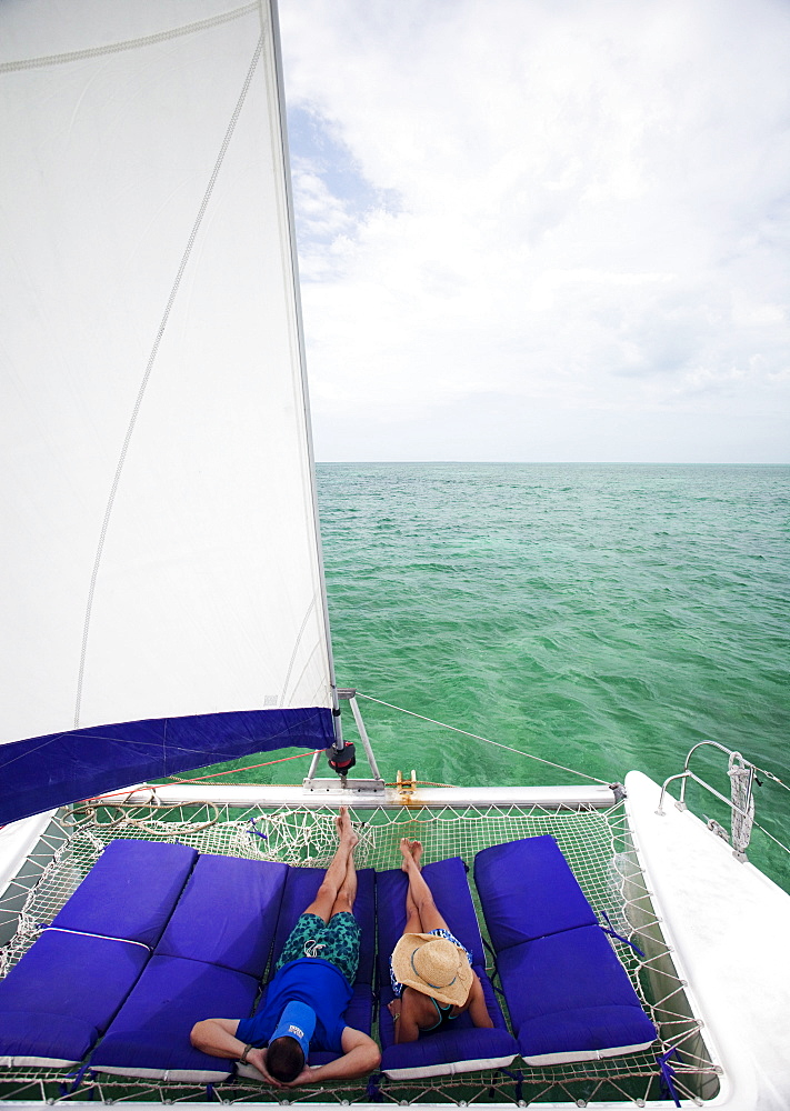 A couple lounge on the front of a catamaran enjoying a cruise in the Caribbean, Belize
