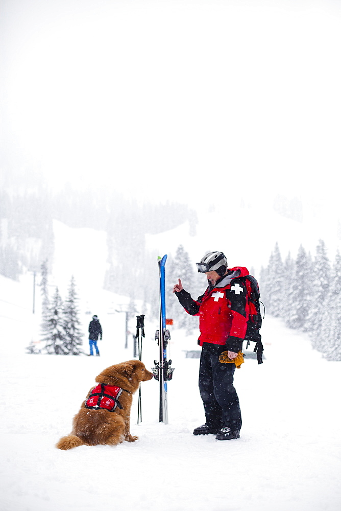 Court Wing, a legendary ski patroller at Steven's Pass, WA with his dog on a snowy day, United States of America