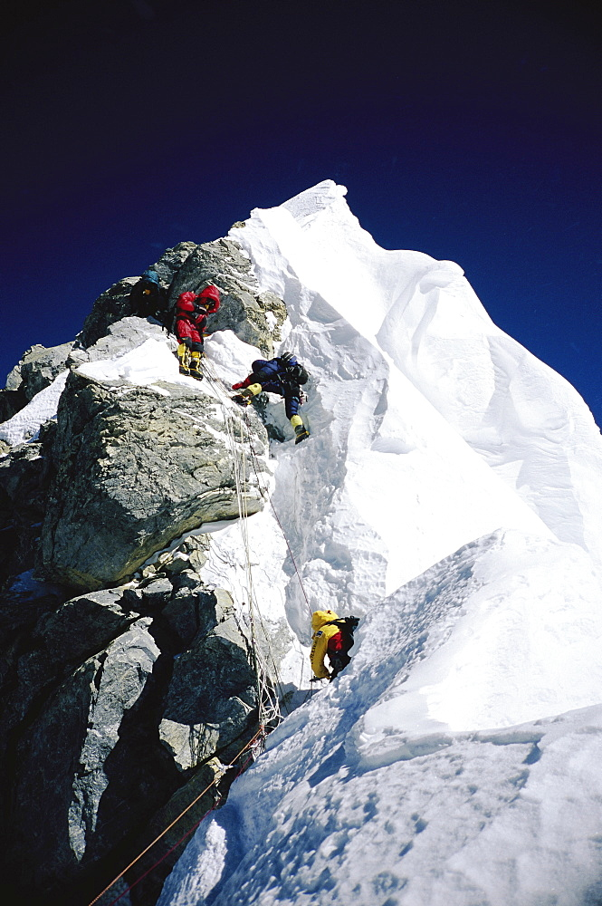 "Mountaineers navigating through the Hillary Step on Mount Everest. The Hillary Step is a nearly vertical part (height around 40 ft) of upper Mount Everest. It lies almost at the top of the mountain, halfway from the ""south summit"" to the summit top, and is the last real challenge before the summit. It is reached by climbing the South East route. It was named after Sir Edmund Hillary, who was the first person, along with Tenzing Norgay, who passed it to reach the summit, Nepal"