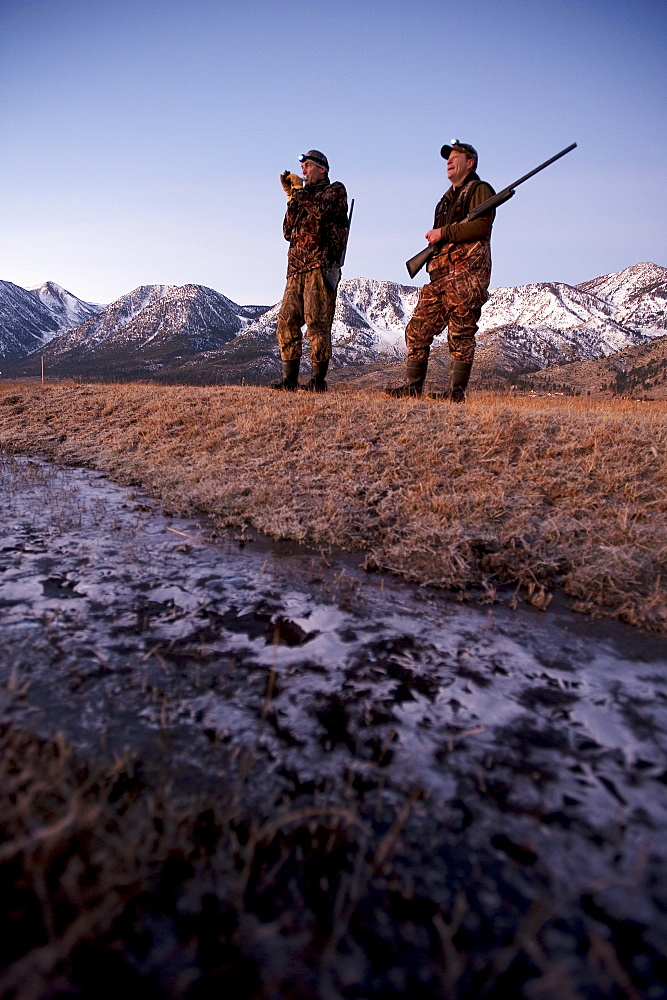 Brad Jackson uses a call as Corey Funk keeps his eyes open for geese as the two men hunt in the early morning in Carson City, NV, United States of America