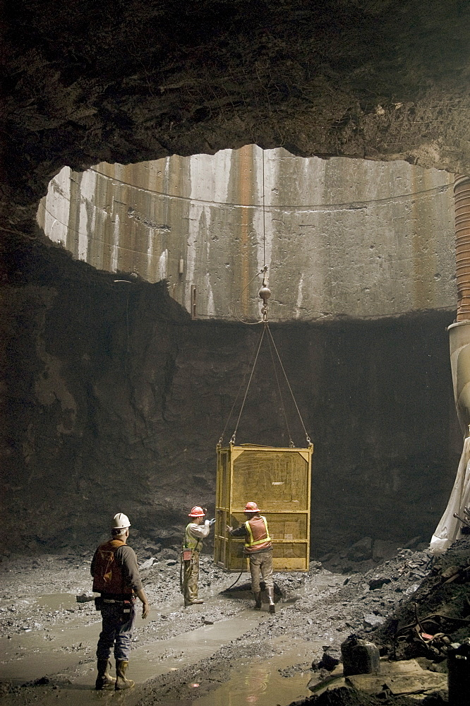 Workers exiting tunnel in crane cage, United States of America