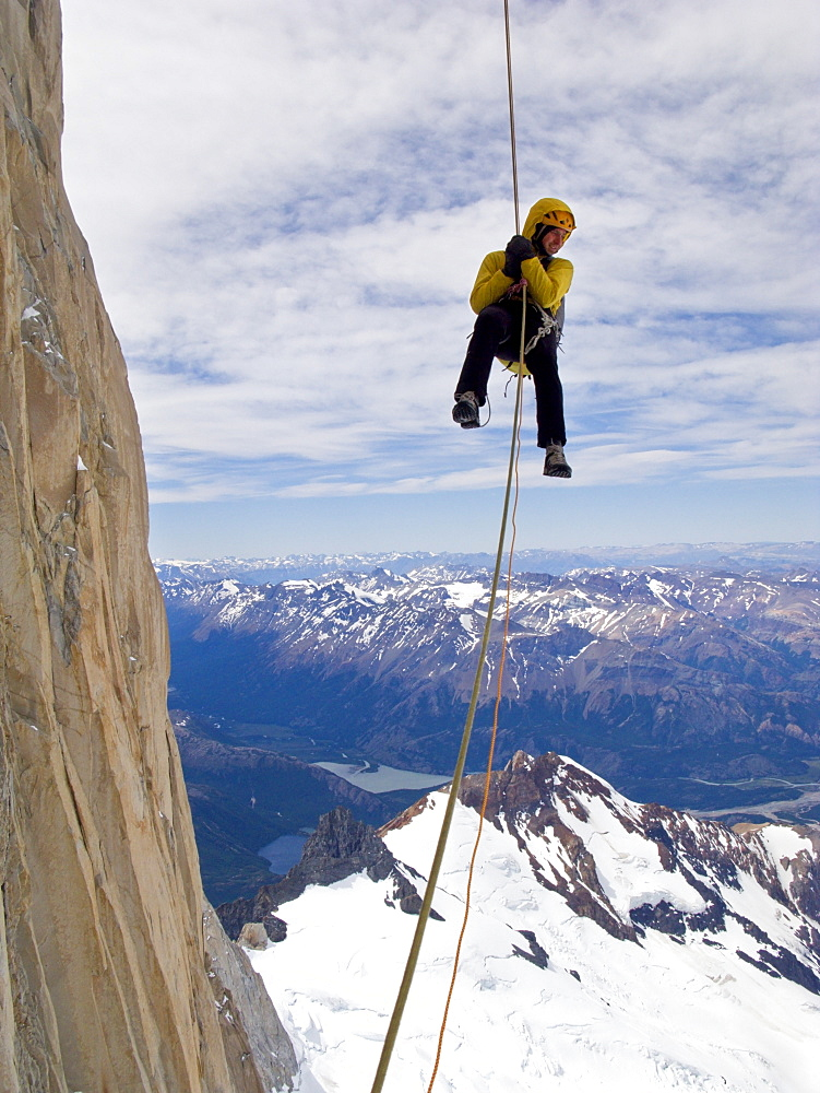 "A climber rappels down Cerro Fitz Roy's south face, with distant peaks and lakes of Argentine Patagonia in the distance. Cerro Fitz Roy is one of the most massive peaks in the Southern Andes, and is a sought after summit by the world's top alpinists. It was named in honor of the captain of Darwin's ship, the Beagle, Captain Robert FitzRoy, who explored the region. The indigenous name for the peak is Chalten, which means ""smoking mountain"". , Argentina"
