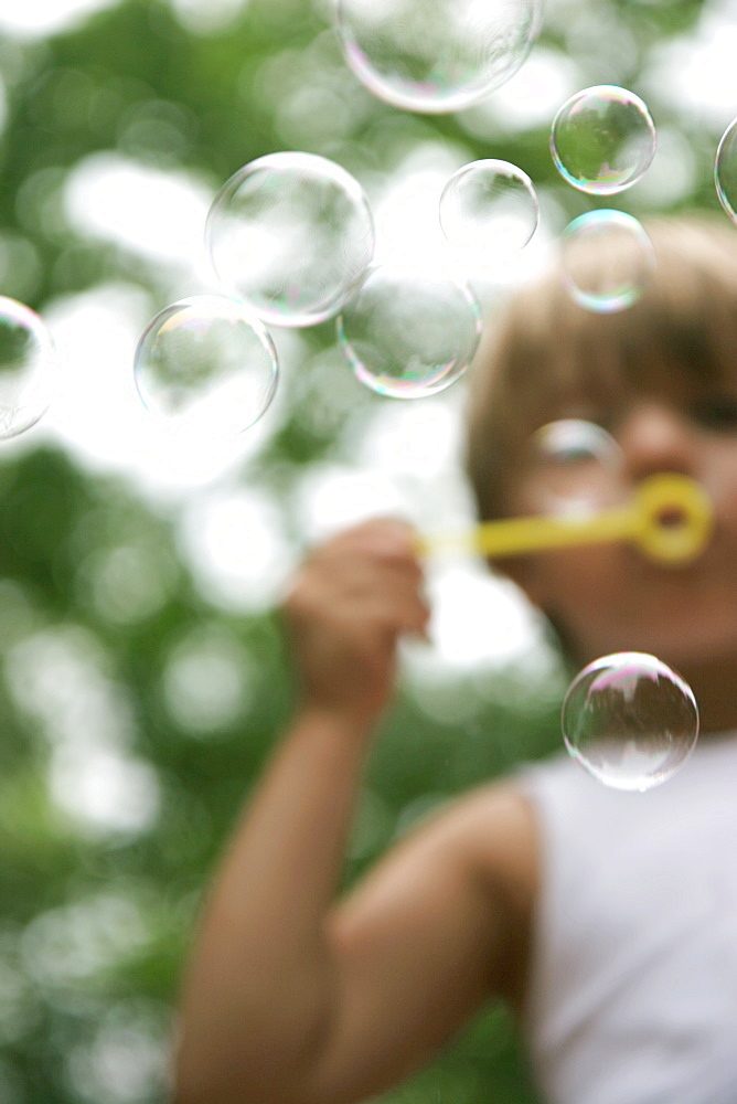 A young boy blows bubbles on his back porch in St. Charles, Missouri on August 3, 2007, United States of America