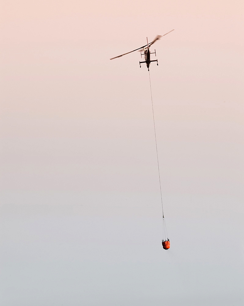 Helicopters pick up water from a reservoir while fighting wildfires in Santa Barbara, California, United States of America