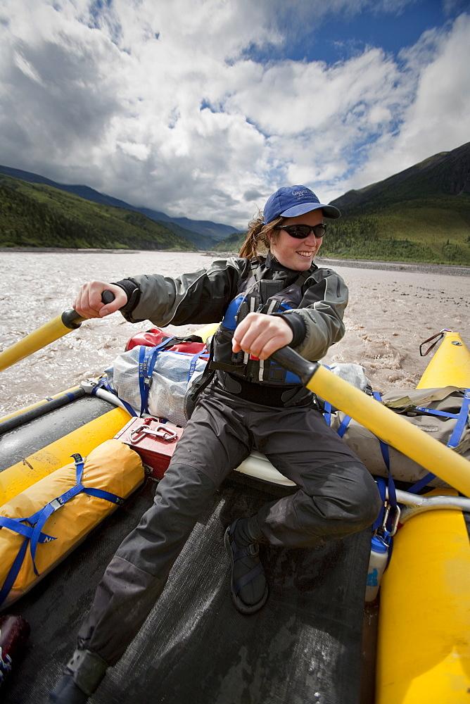 A woman rowing a raft down the Jacksina river, Wrangell-St. Elias National Park, Alaska.