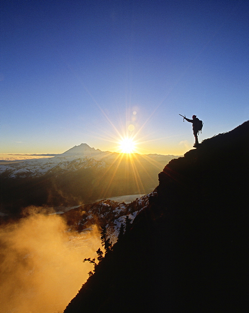 A climber celebrates a beautiful winter day high above the clouds on Goat Mtn, North Cascades, Washington.