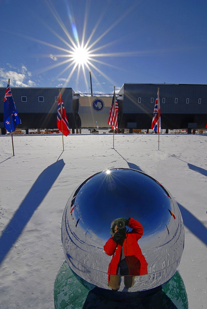 A man photographs himself in the reflection of the South Pole memorial pole.