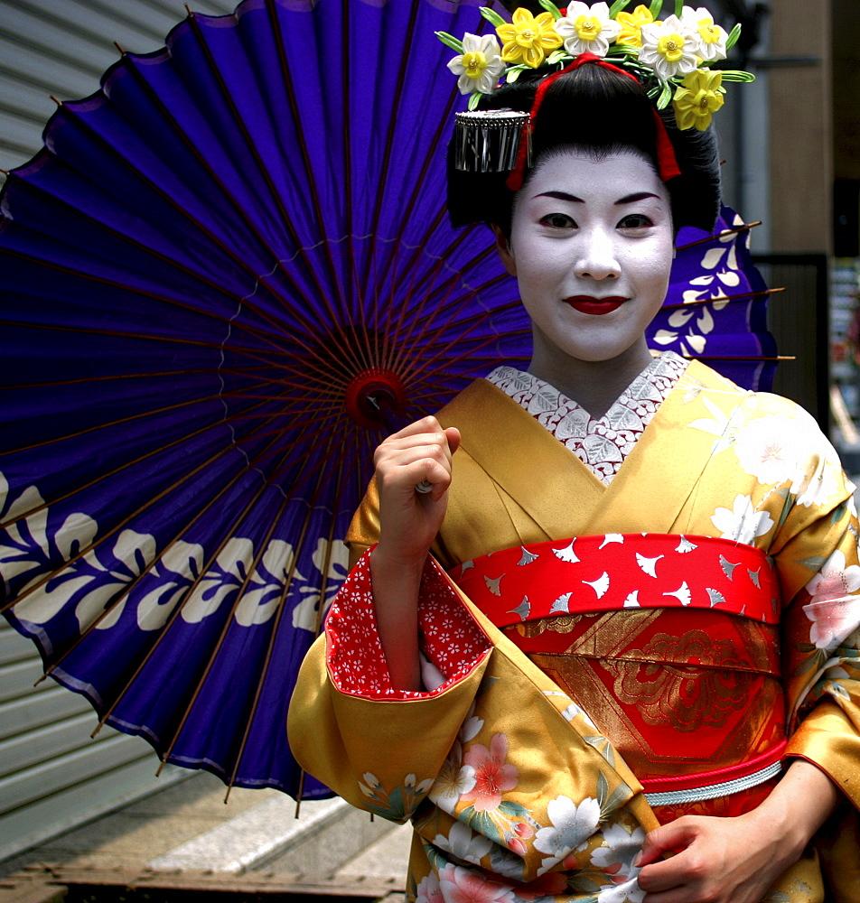 A Geiko (Geisha) poses on a street in Kyoto, Japan.