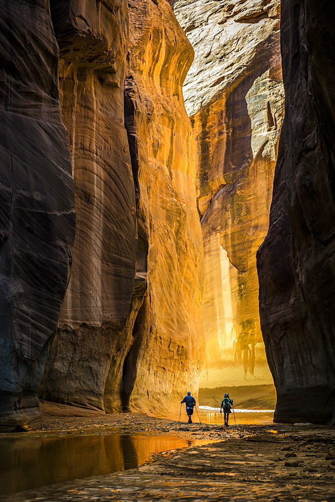 Two people hiking in a canyon.