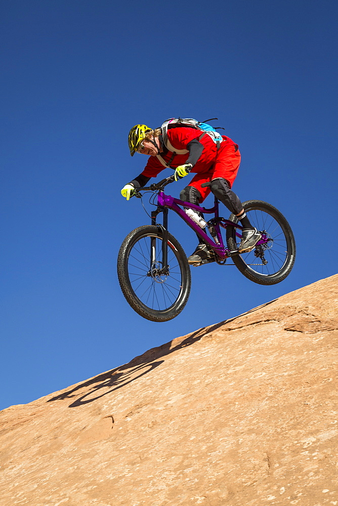 A man mountain biking on the slickrock trail, Moab, Utah.