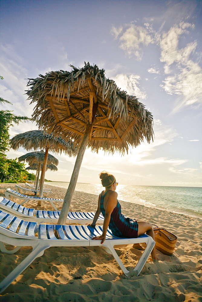 A young woman relaxing on the beach under a beach umbrella in Cayo Coco, Cuba