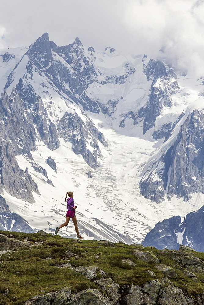 Girl trail running in Chamonix around the Chesery lake, Le des Cheserys, Haute Savoie, France.