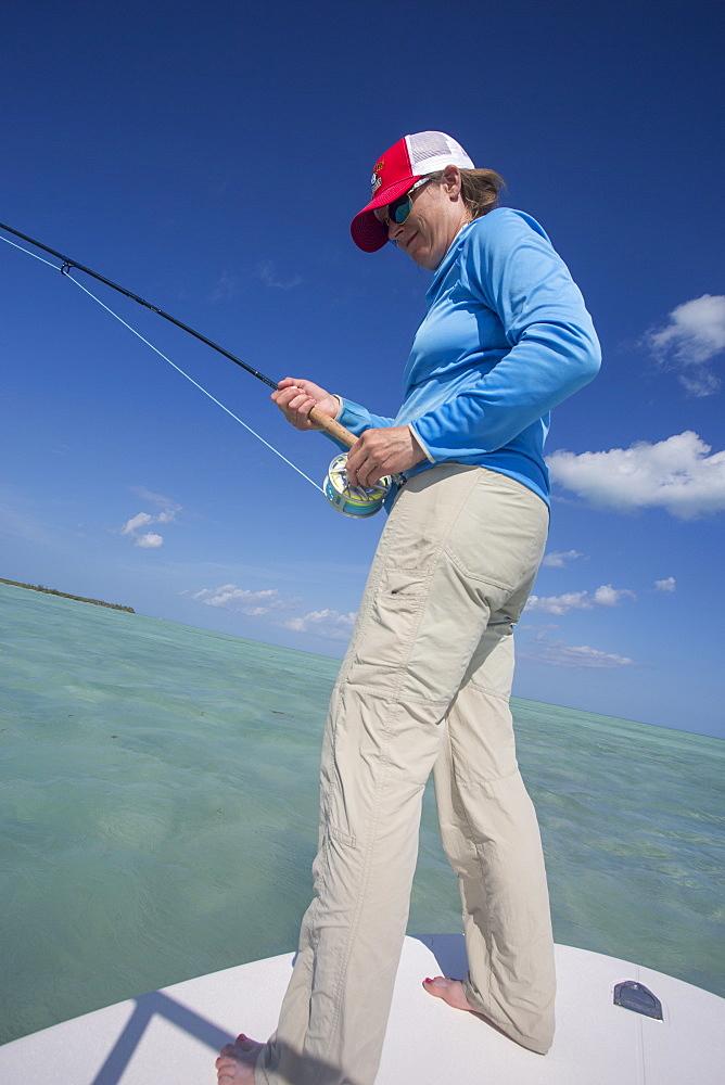 A woman reels in a bonefish. Cayo Cruz, Cuba, 2016.